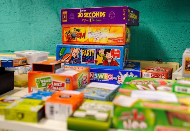 Pile of boardgames presented on a table.