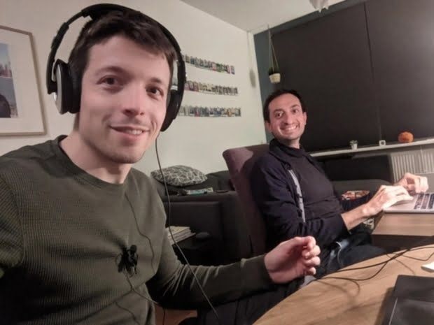 DLC members Roben and Beppe sitting behind a desk with headphones on presenting the radio show while smiling at the camera.
