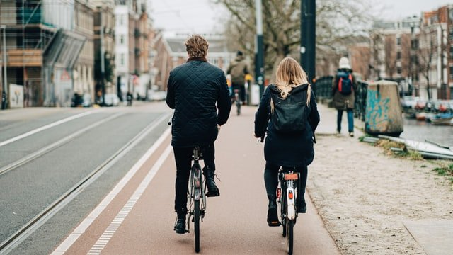 A back shot from a man and a woman cycling next to each other on a bicycle lane.