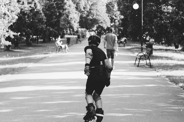 A back shot from a man inline-skating in a park.